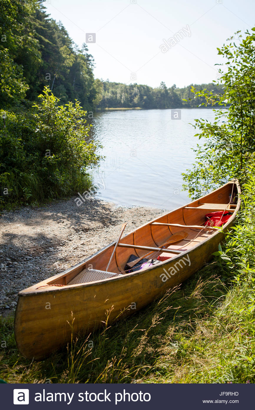 A wooden canoe sits on the shoreline of the Kennebec River in central Maine. - Stock Image