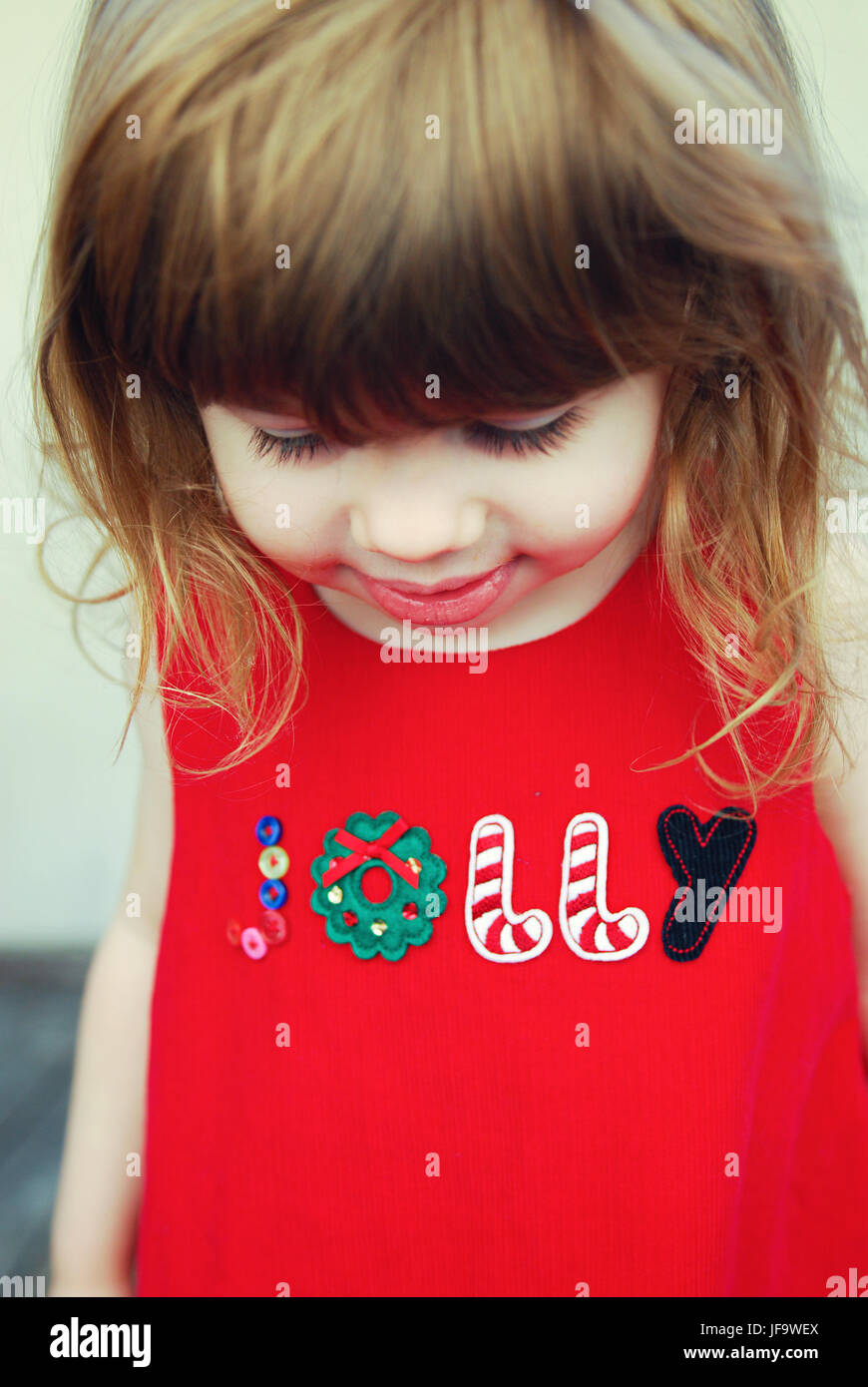 Happy toddler wearing jolly christmas dress - Stock Image