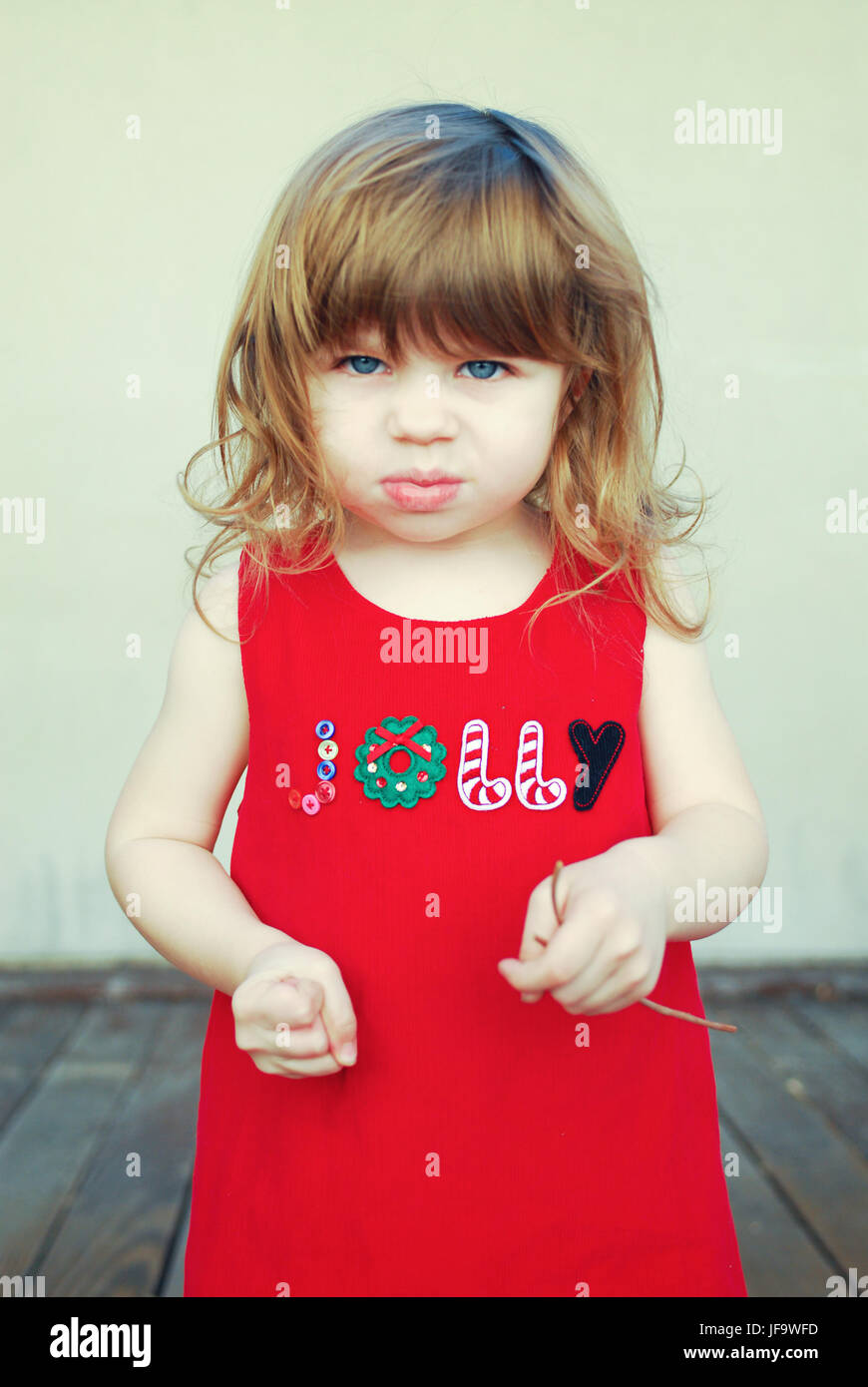 Angry little girl wearing jolly Christmas dress - Stock Image