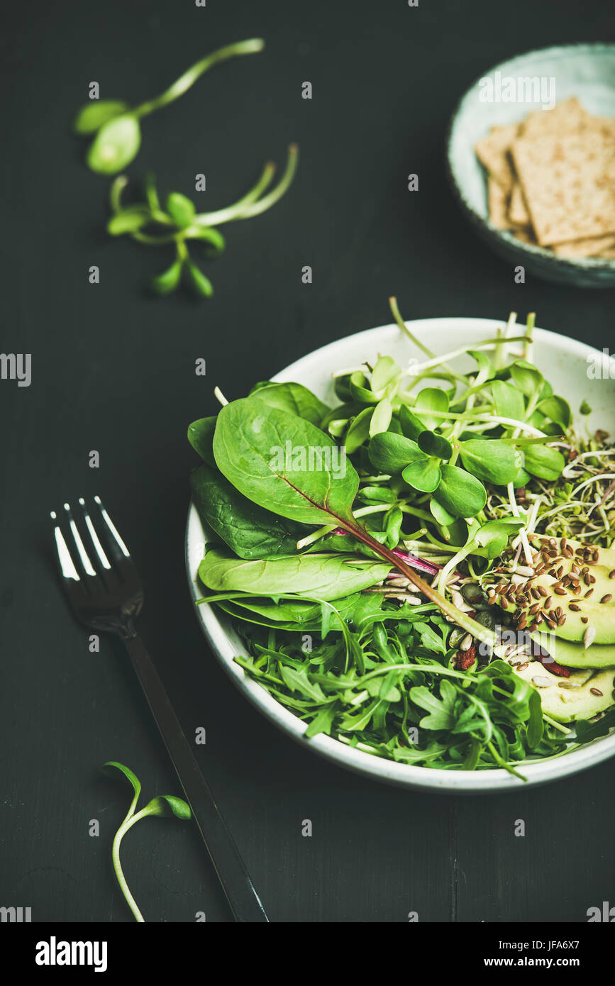 Breakfast with spinach, arugula, avocado, seeds and sprouts in bowl Stock Photo