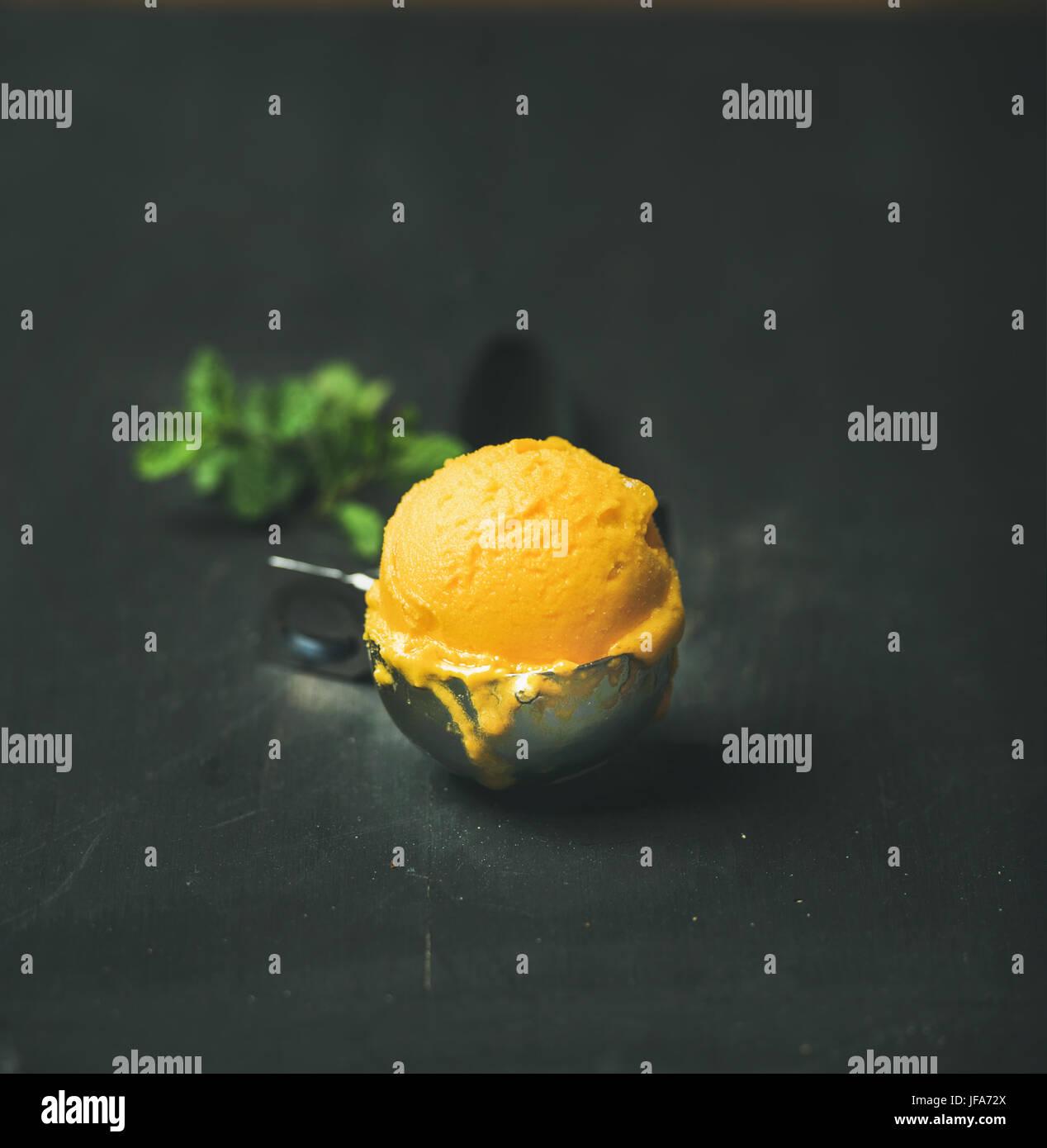 Mango sorbet ice cream scoop, square crop, copy space - Stock Image