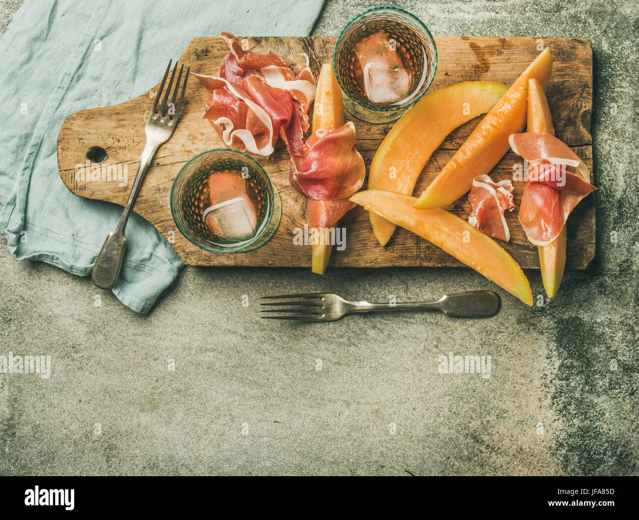 Flatlay of rose wine, prosciutto ham, melon, copy space - Stock Image