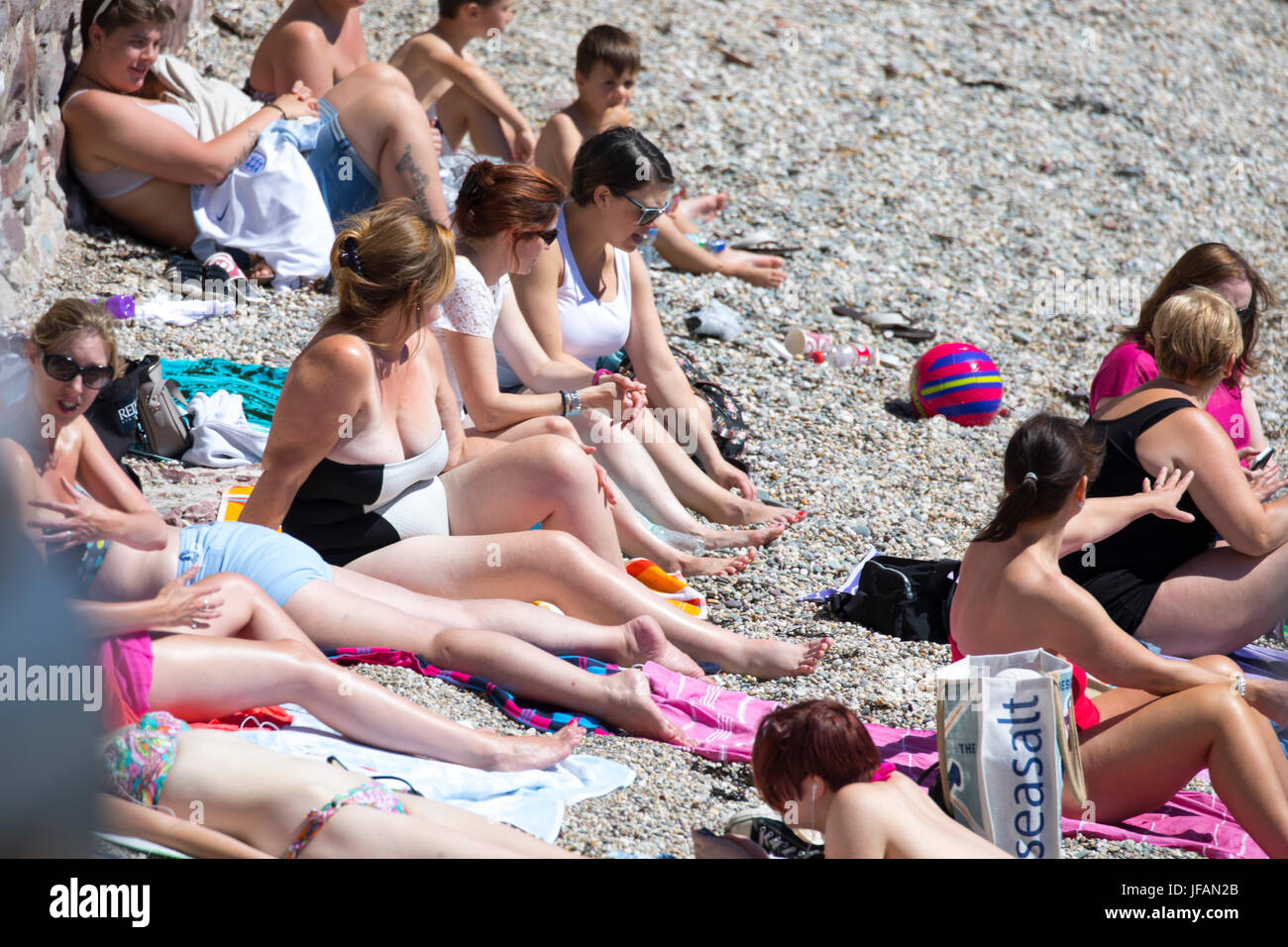 Sun bathers at the popular seaside village of Kingsand in Cornwall, England sunbathing on the pebble beach at the - Stock Image