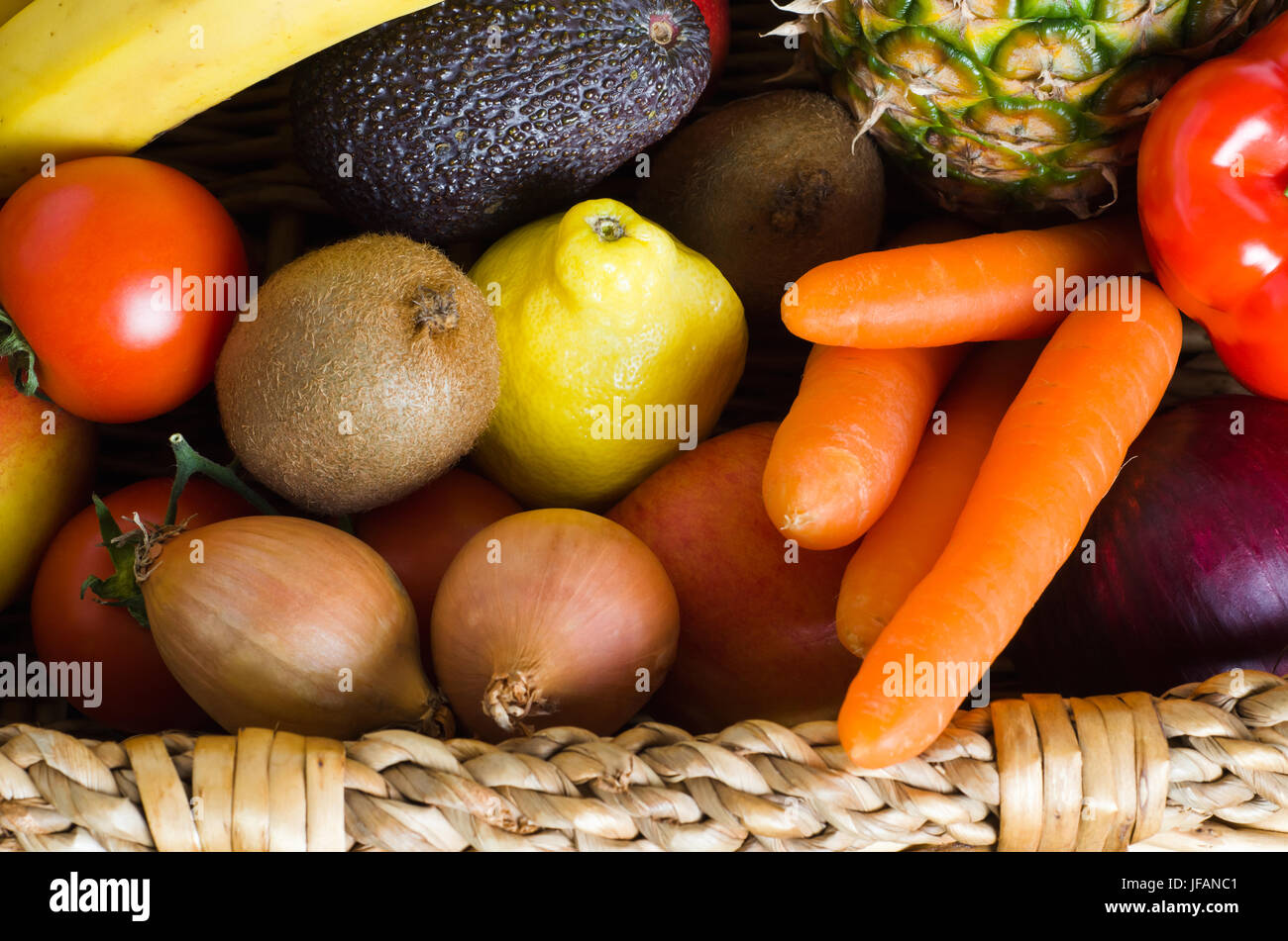 Overhead shot of a basket crammed with raw, fresh, colourful fruit and vegetables.  Landscape orientation. - Stock Image
