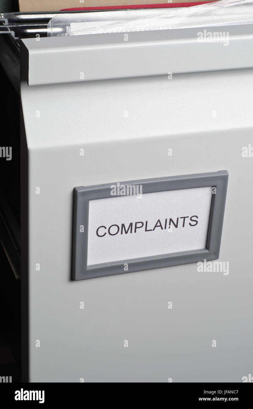 An opened filing cabinet drawer labeled 'Complaints', exposing hanging files and documents within.  Portrait - Stock Image
