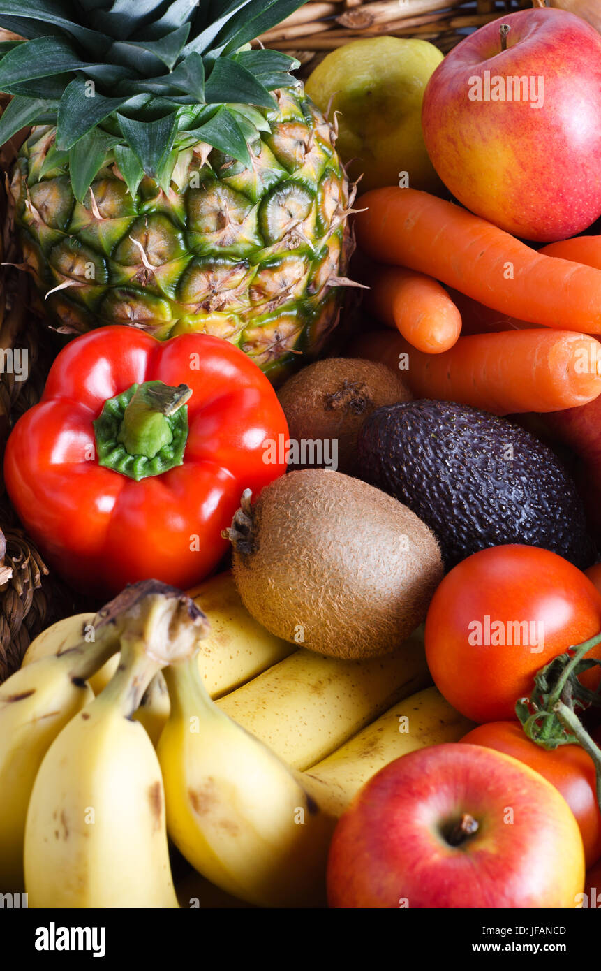 Overhead shot of a selection of fresh fruit and vegetables in a wicker basket.  Portrait orientation. - Stock Image
