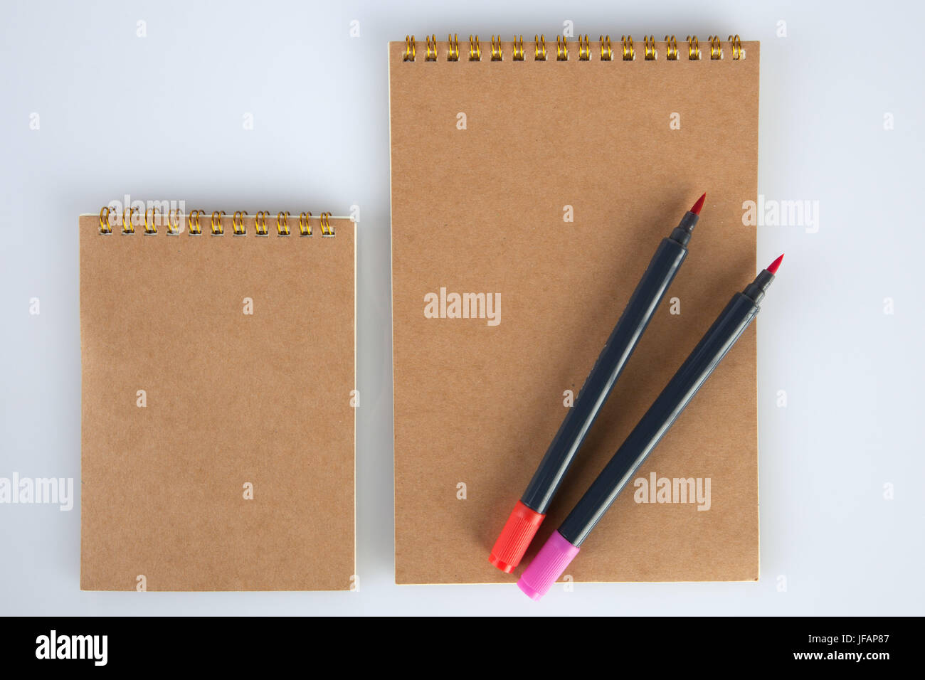 Two spiral notepads big and small with two markers for mockups. Top view with copy space Stock Photo