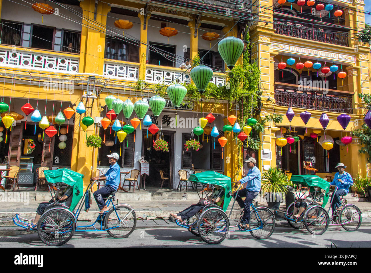 Tourists on a cyclo tour, colorful lanterns in Hoi An, Vietnam - Stock Image