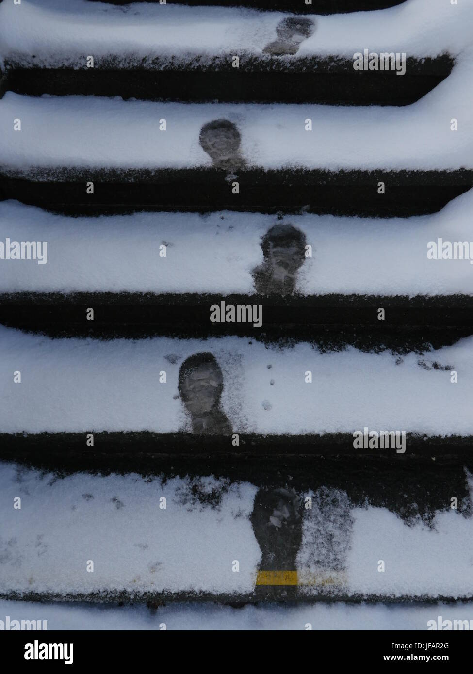 Closeup of footsteps in snow going forward - Stock Image