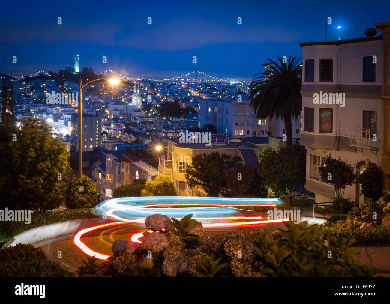 Lombard Street, the 'crookedest street in the world', at night, with light trails from passing cars, in - Stock Image