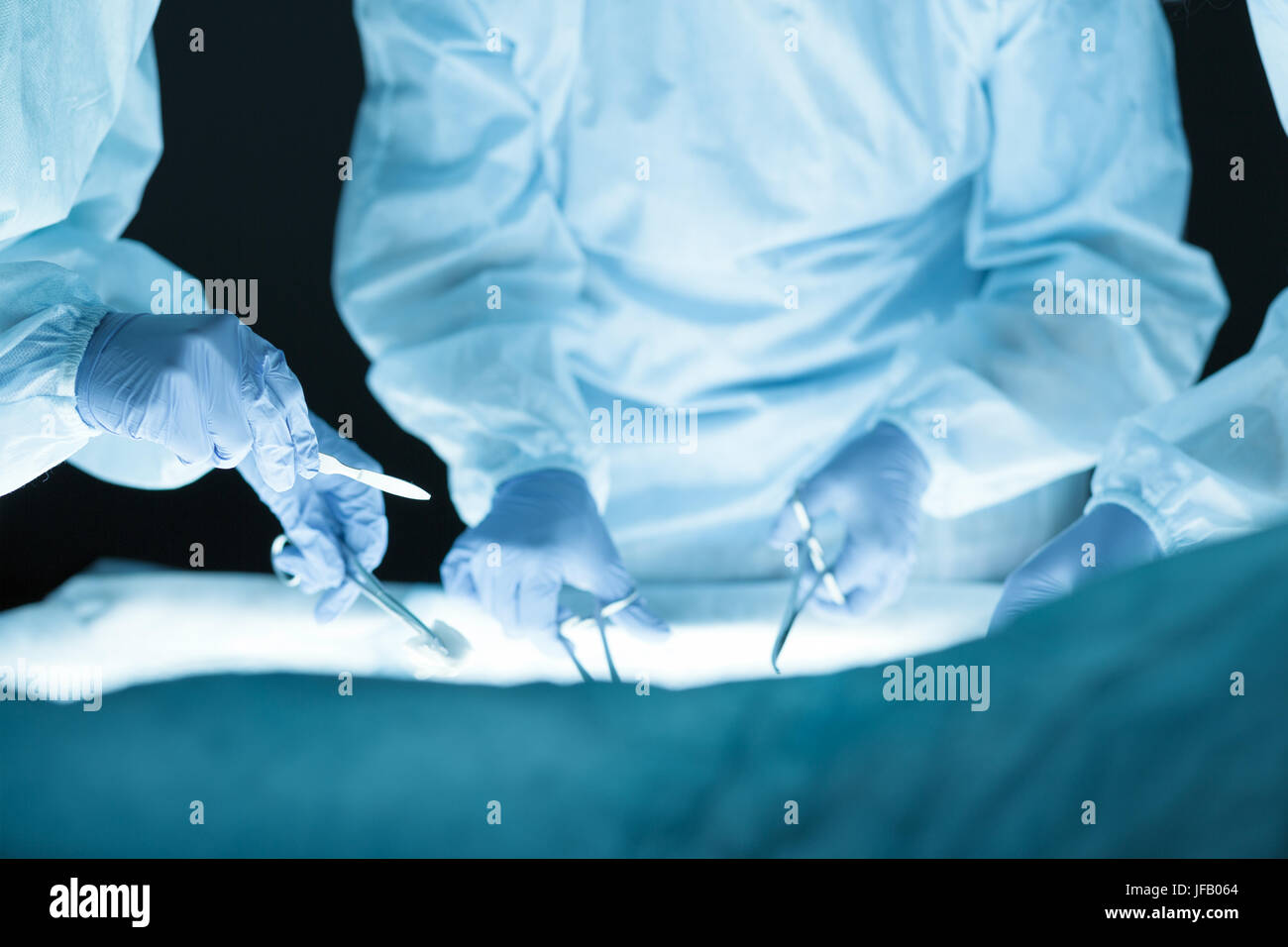 Medical team performing operation. Group of surgeon at work in operating theatre. Hands close-up view - Stock Image