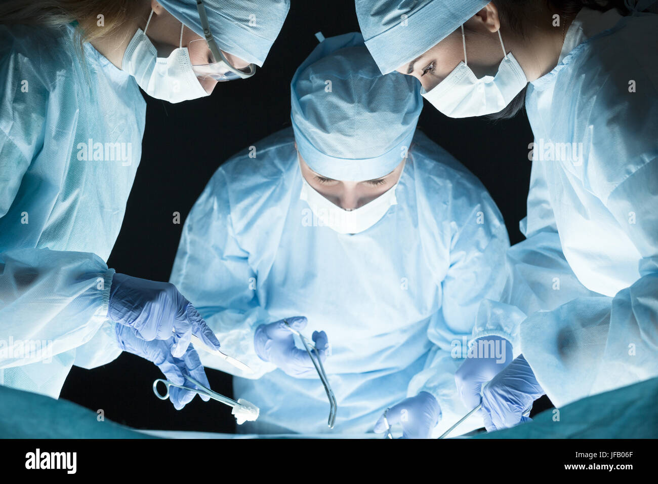 Medical team performing operation. Group of surgeon at work in operating theatre - Stock Image