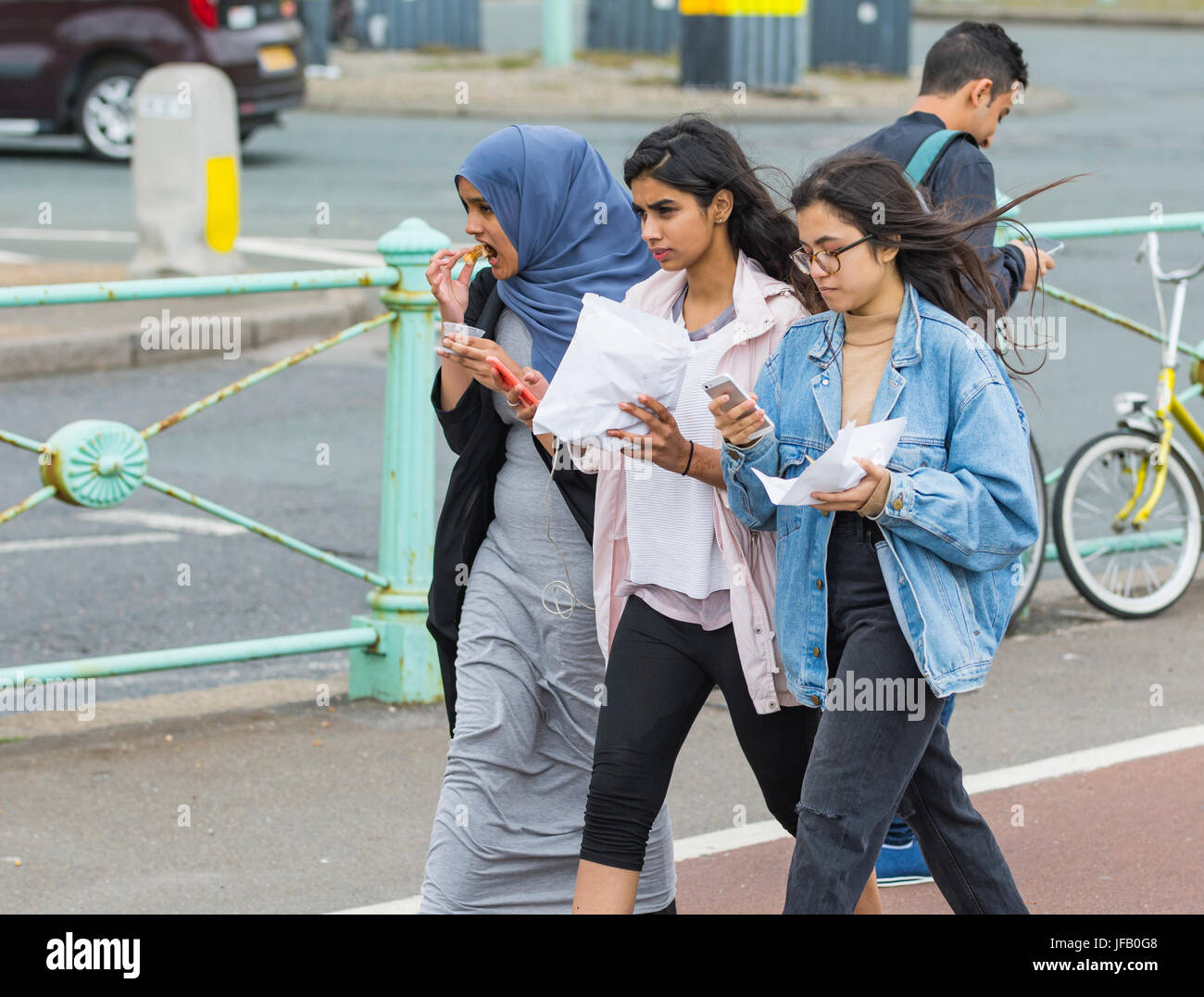 Friends walking along while eating and looking at their smartphones. - Stock Image