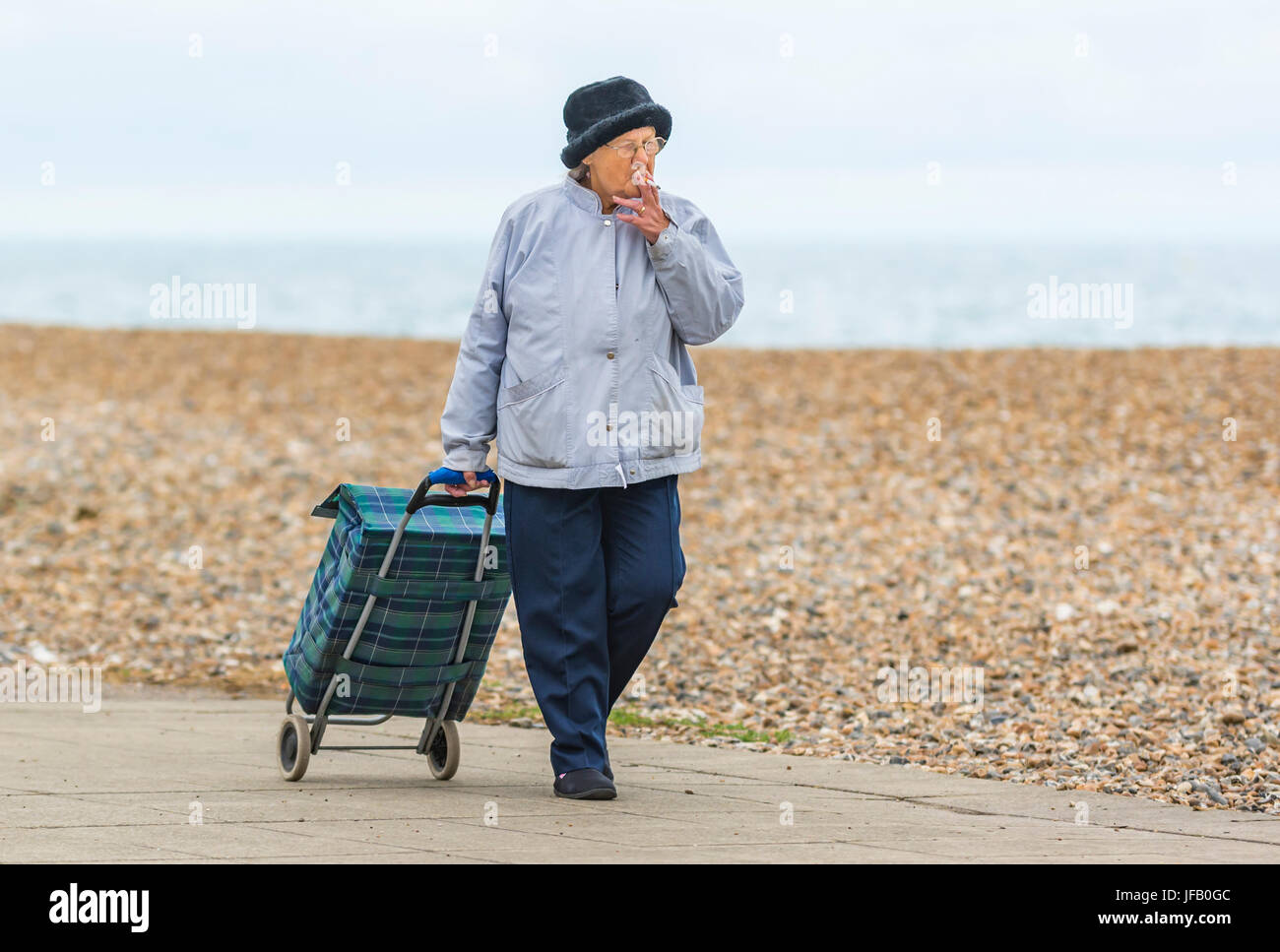 Elderly lady pulling a shopping trolley while smoking. - Stock Image