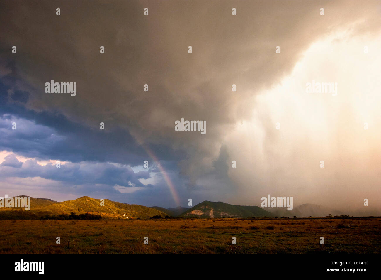 extreme weather landscape with dramatic storm clouds, heavy rain and rainbow in sunset light Stock Photo