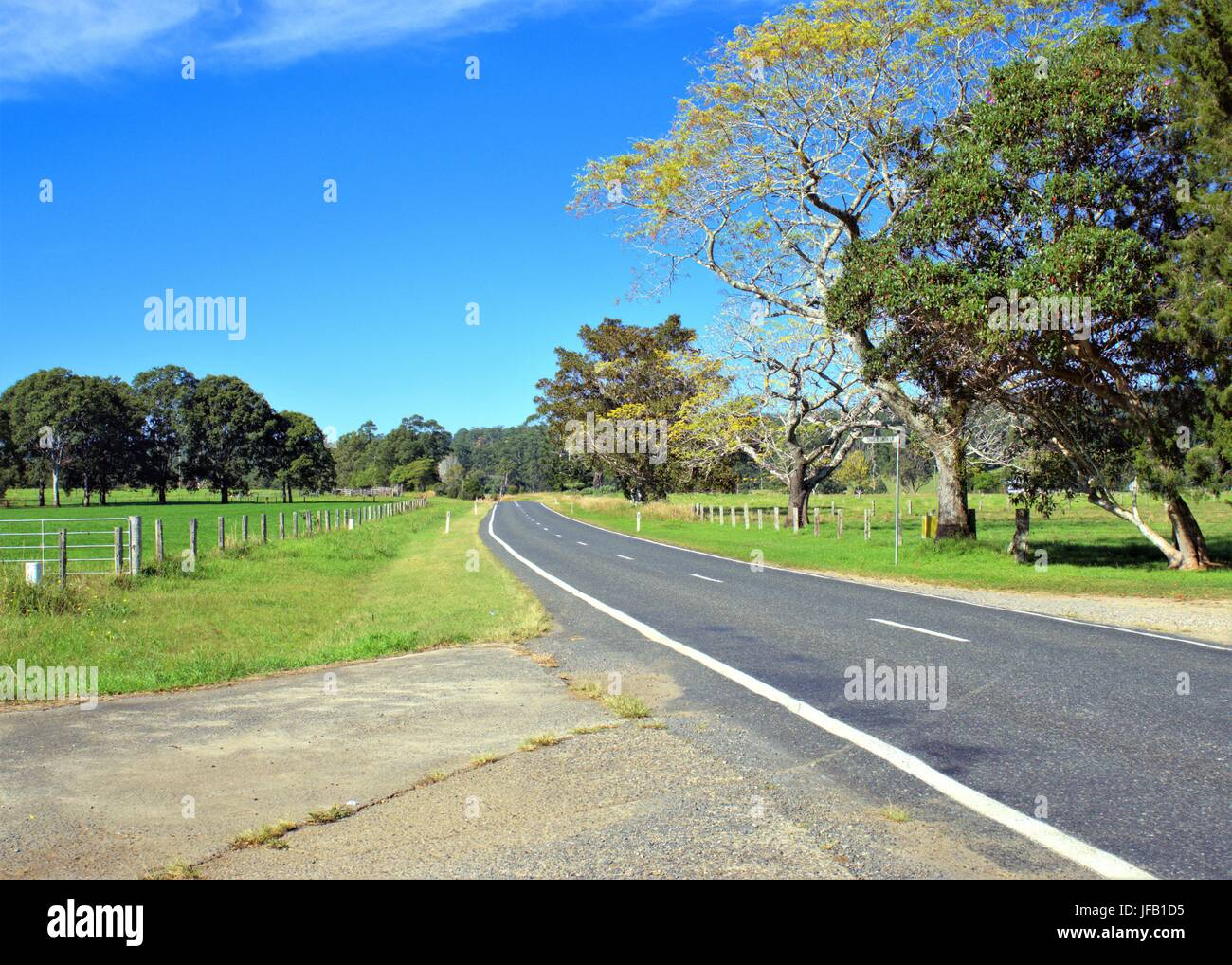 Beautiful country road with green grass, trees and blue sky and mountain top in the far background in New South - Stock Image