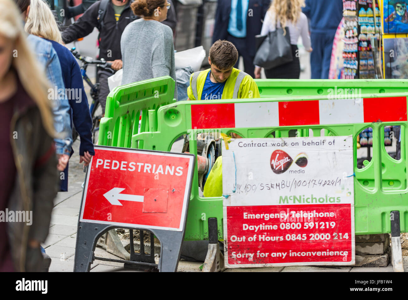 Pavement works. Workers on a pavement in the UK with barriers directing pedestrians around it. Stock Photo