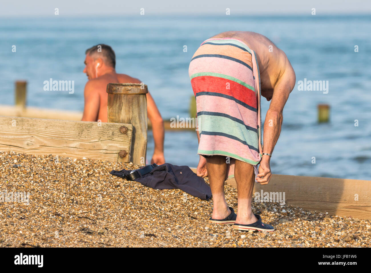 Man on a beach covered with a towel while changing. - Stock Image