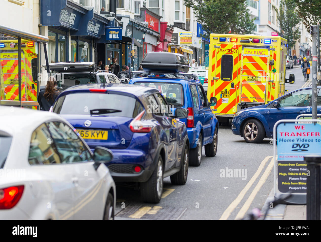 Ambulance with blue lights on parked in a road blocking traffic in the UK. Stock Photo