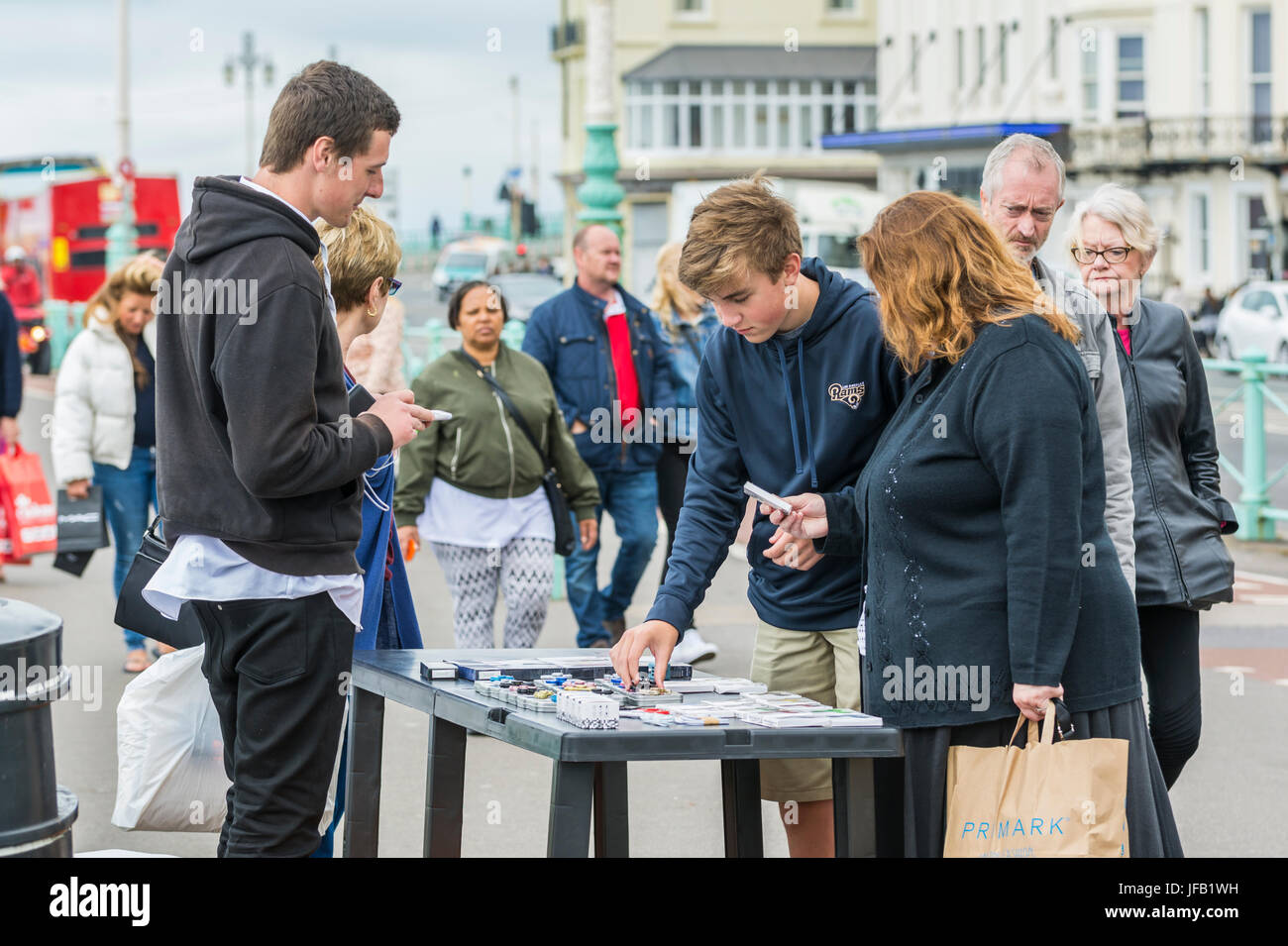 Street trader. Man with a stool in the street selling fidget spinners in the UK. - Stock Image