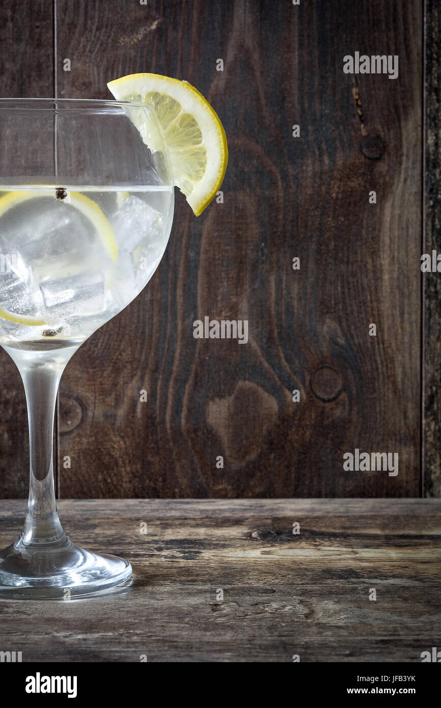 Glass of gin and tonic with lemon on wooden background - Stock Image