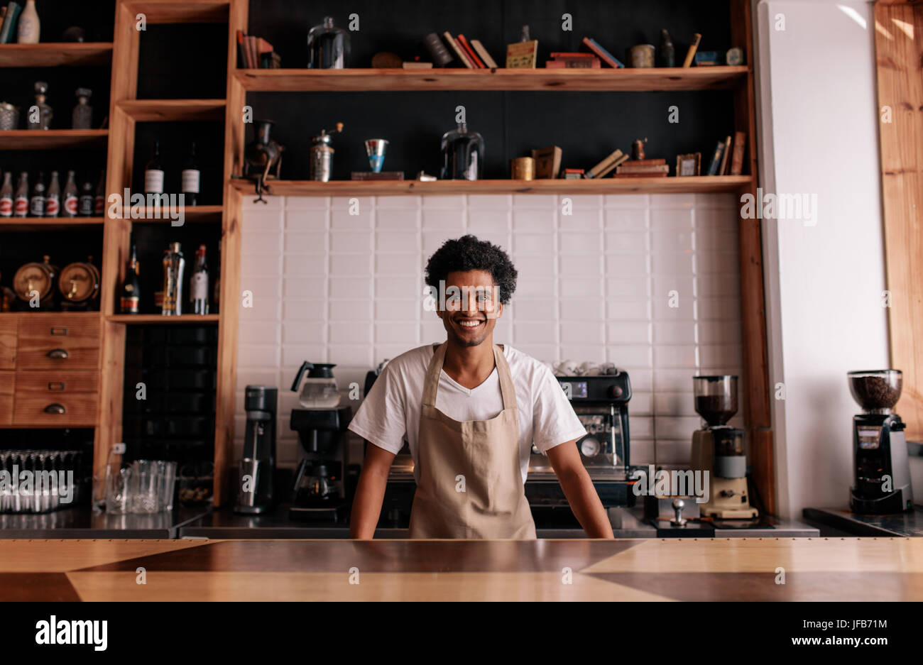 Portrait of professional barista standing at cafe counter. African man in apron looking at camera and smiling. - Stock Image