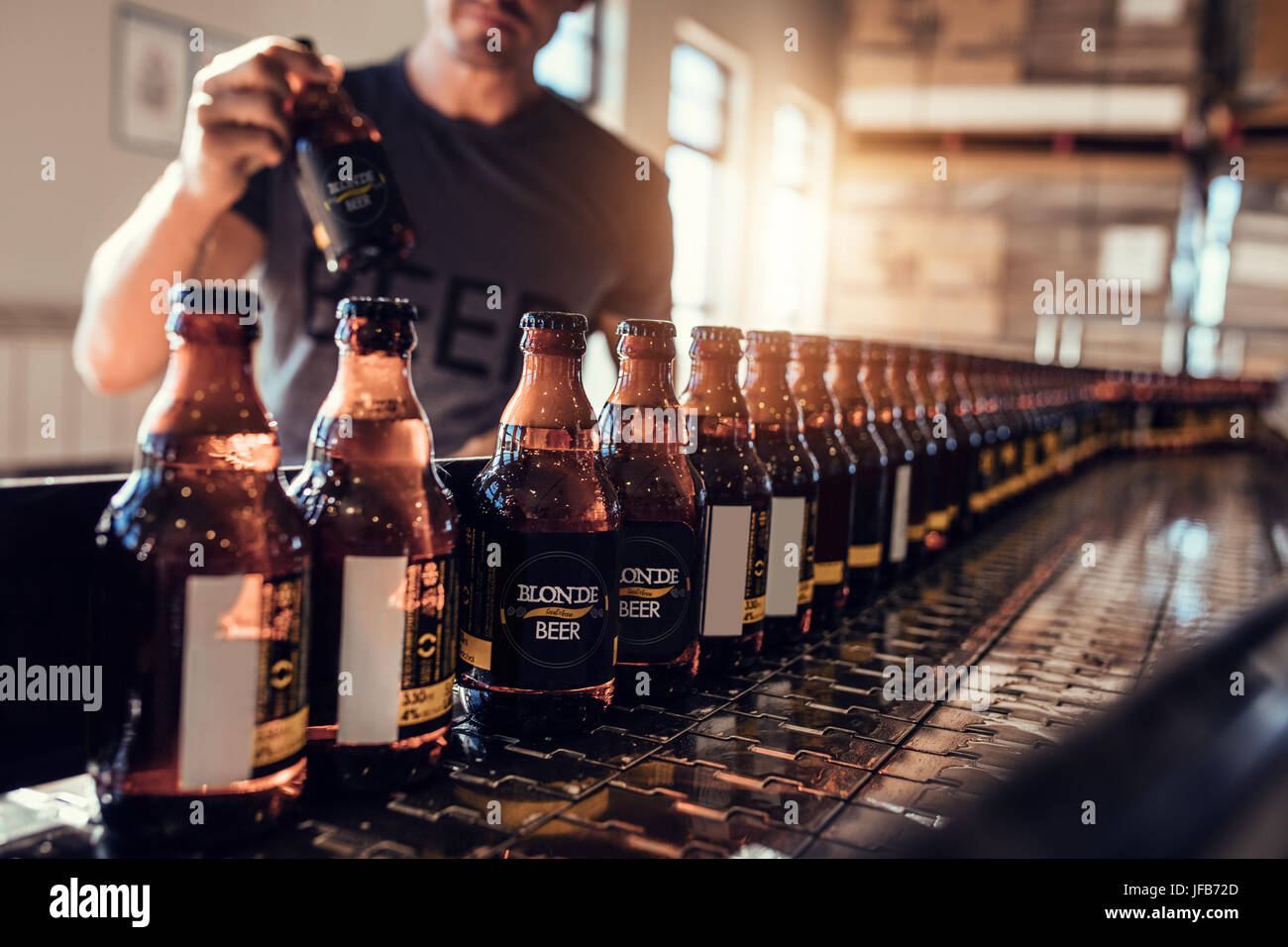 Conveyor with beer bottles moving in brewery factory. Young man supervising the beer bottling process and checking - Stock Image