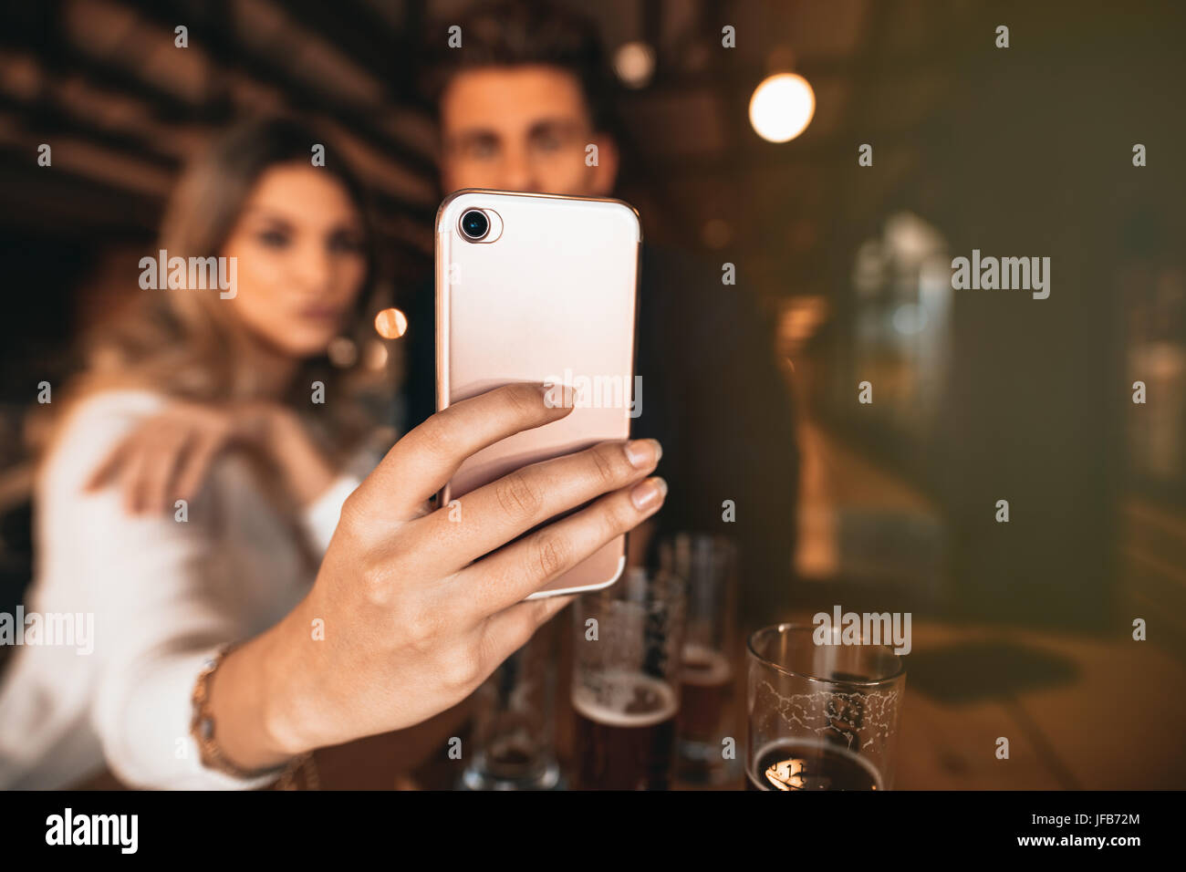 Close up of couple sitting in the bar and taking a selfie with smart phone. Focus on mobile phone in hand of woman. - Stock Image