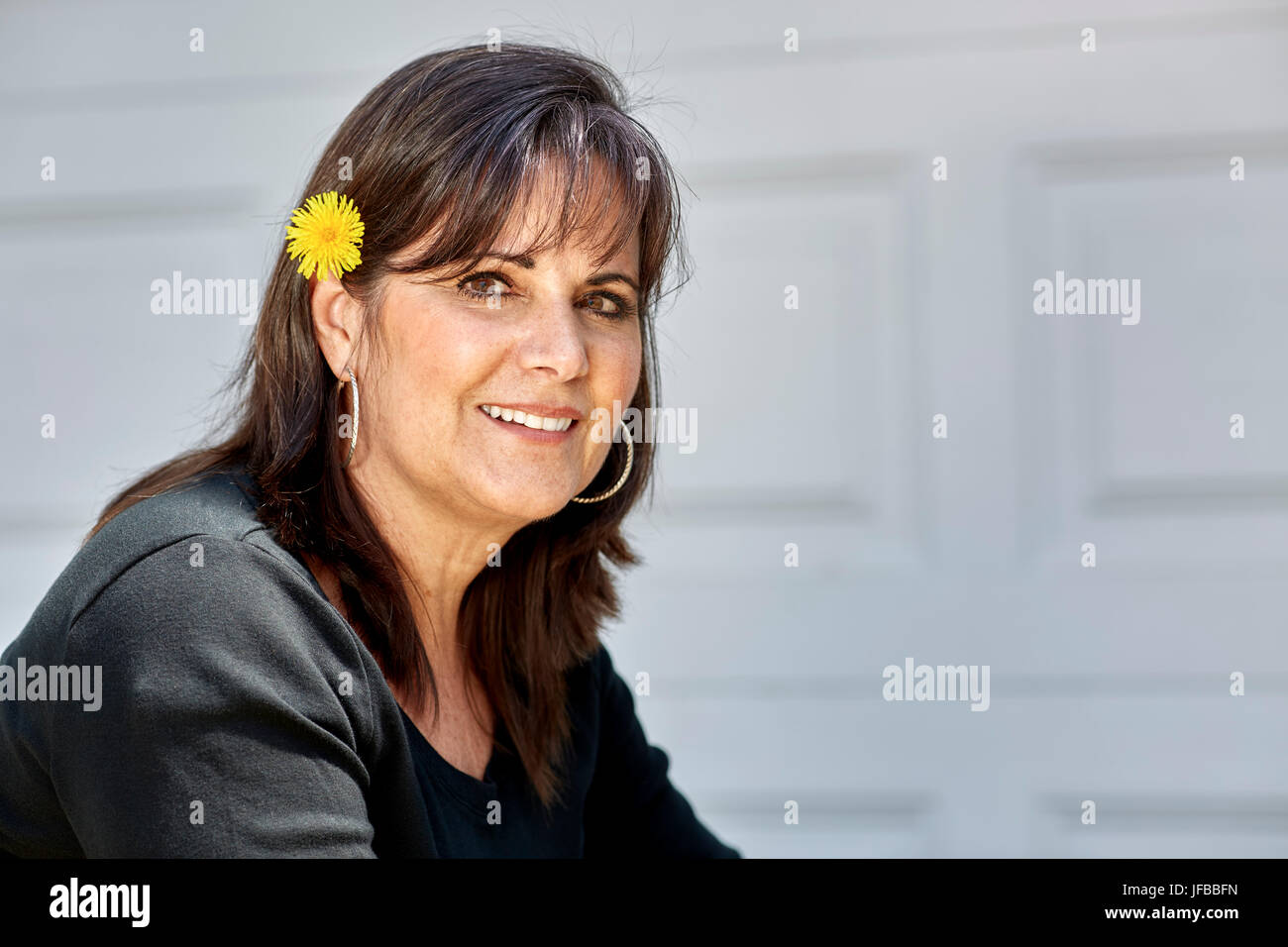 Happy middle aged woman smiling looking towards  camera with a yellow dandelion flower in her hair tucked behind - Stock Image