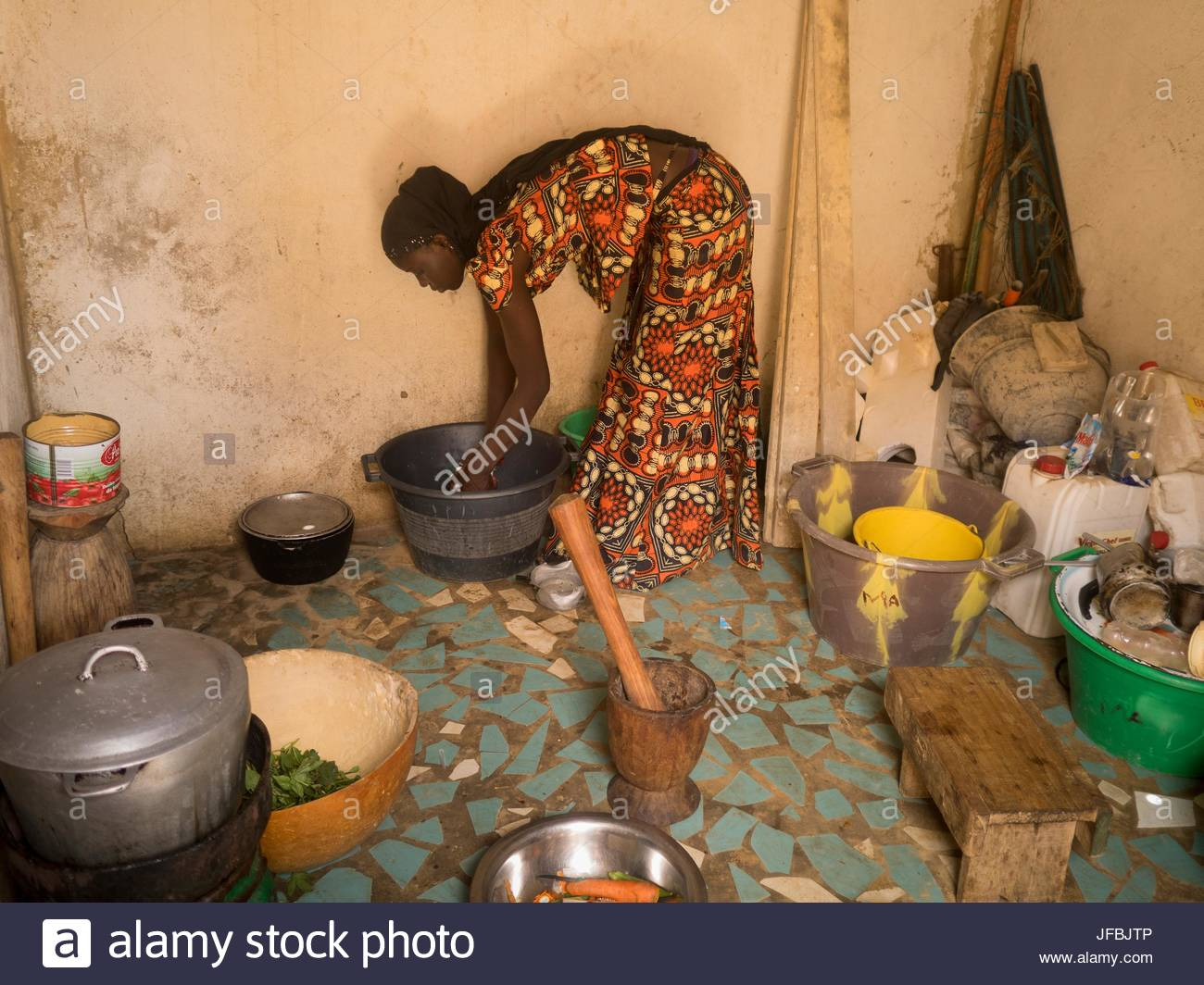 A 15 year old girl cooking for her family. - Stock Image