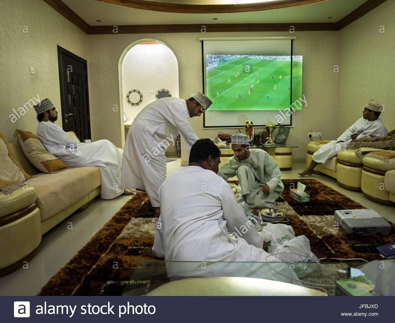 Men eat dinner and watch a soccer match on a wide screen TV. - Stock Image