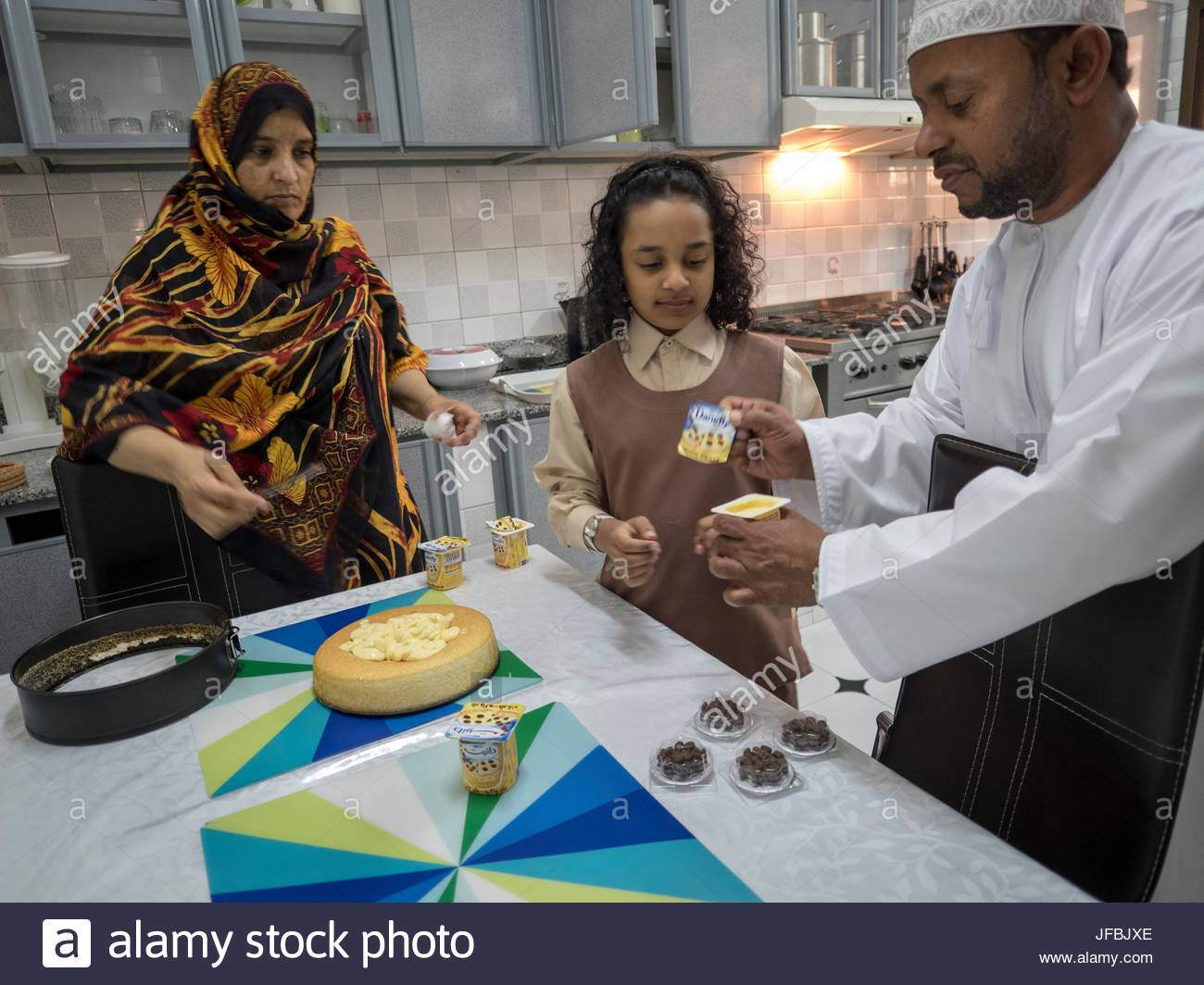 A 10 year old girl in the kitchen with her parents. - Stock Image