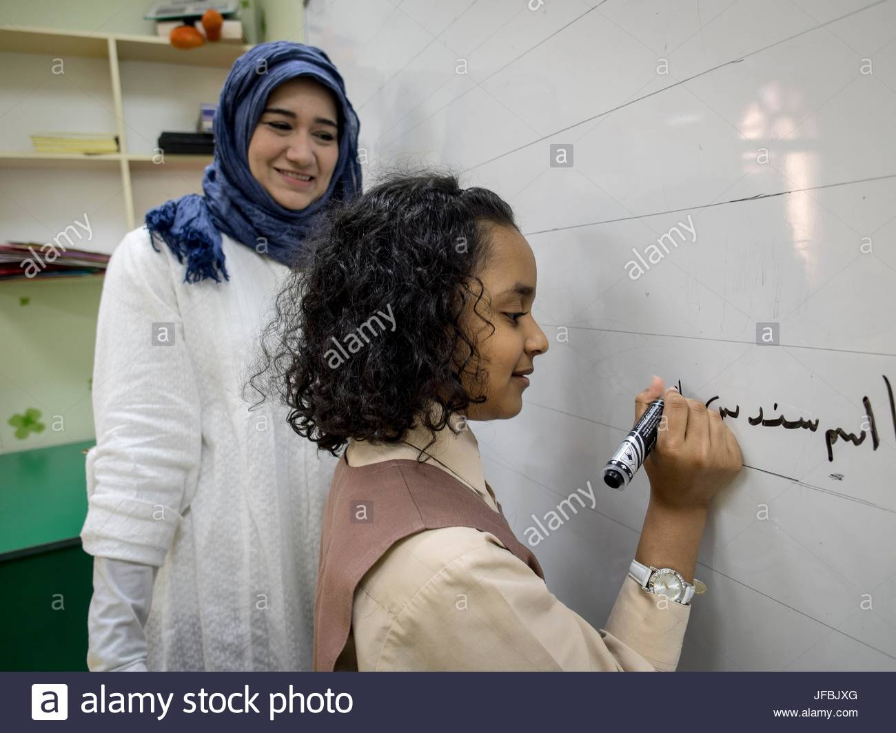 A teacher watches a 10 year old girl writing on a board. - Stock Image