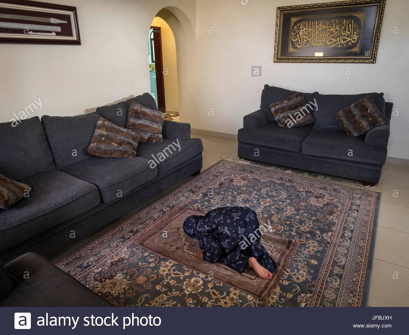 A 10 year old Muslim girl praying at home. - Stock Image