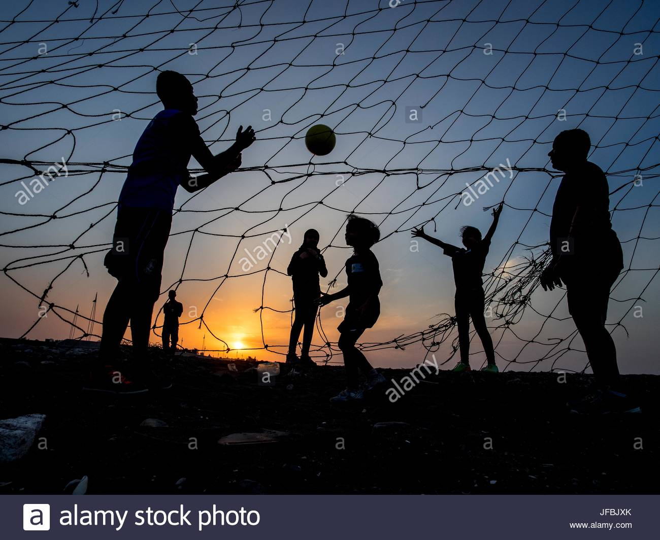 People playing soccer at sunset. - Stock Image