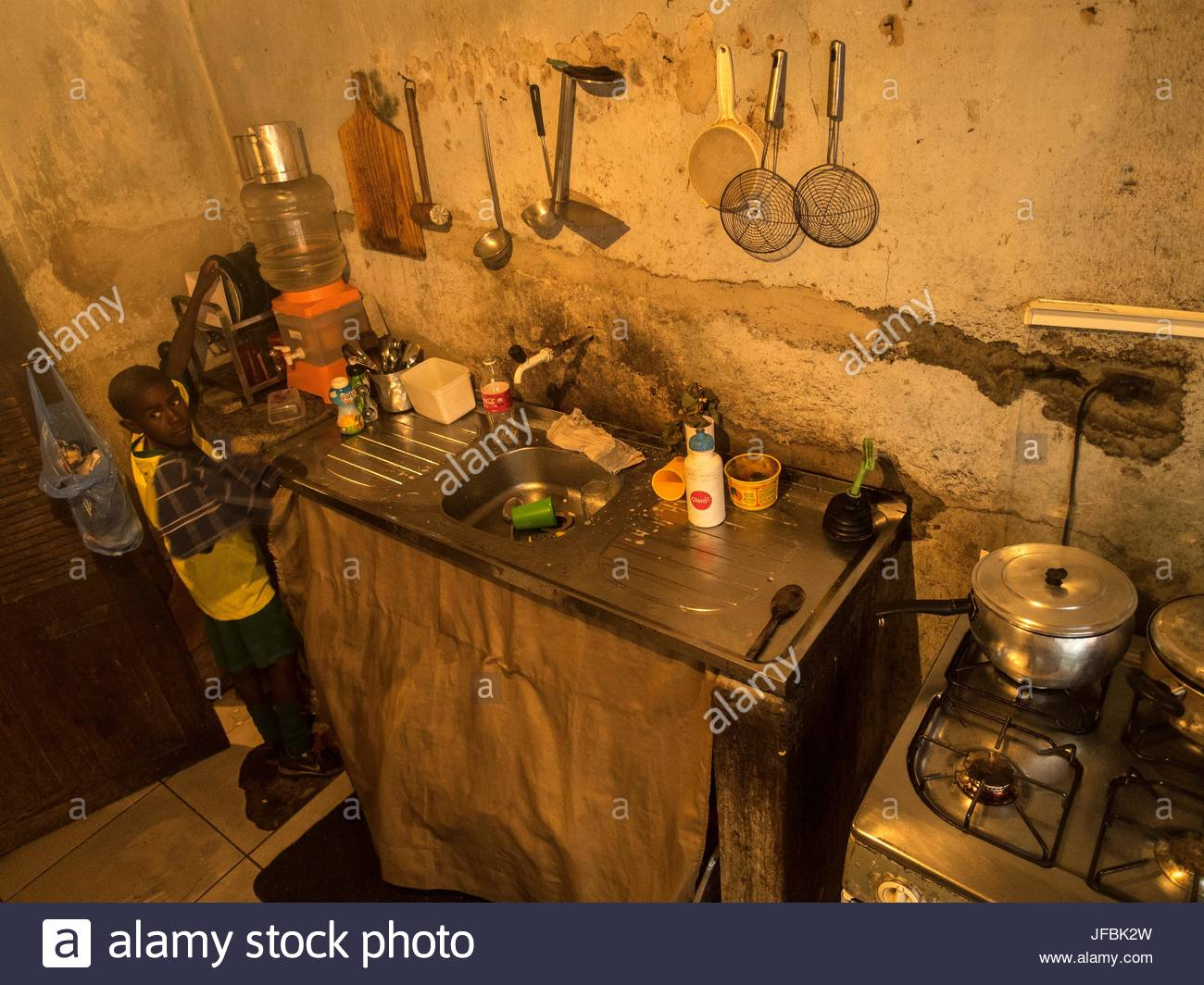 A boy in a basic kitchen at his home in Favela Nova Holanda, a slum neighborhood in Rio de Janeiro. - Stock Image