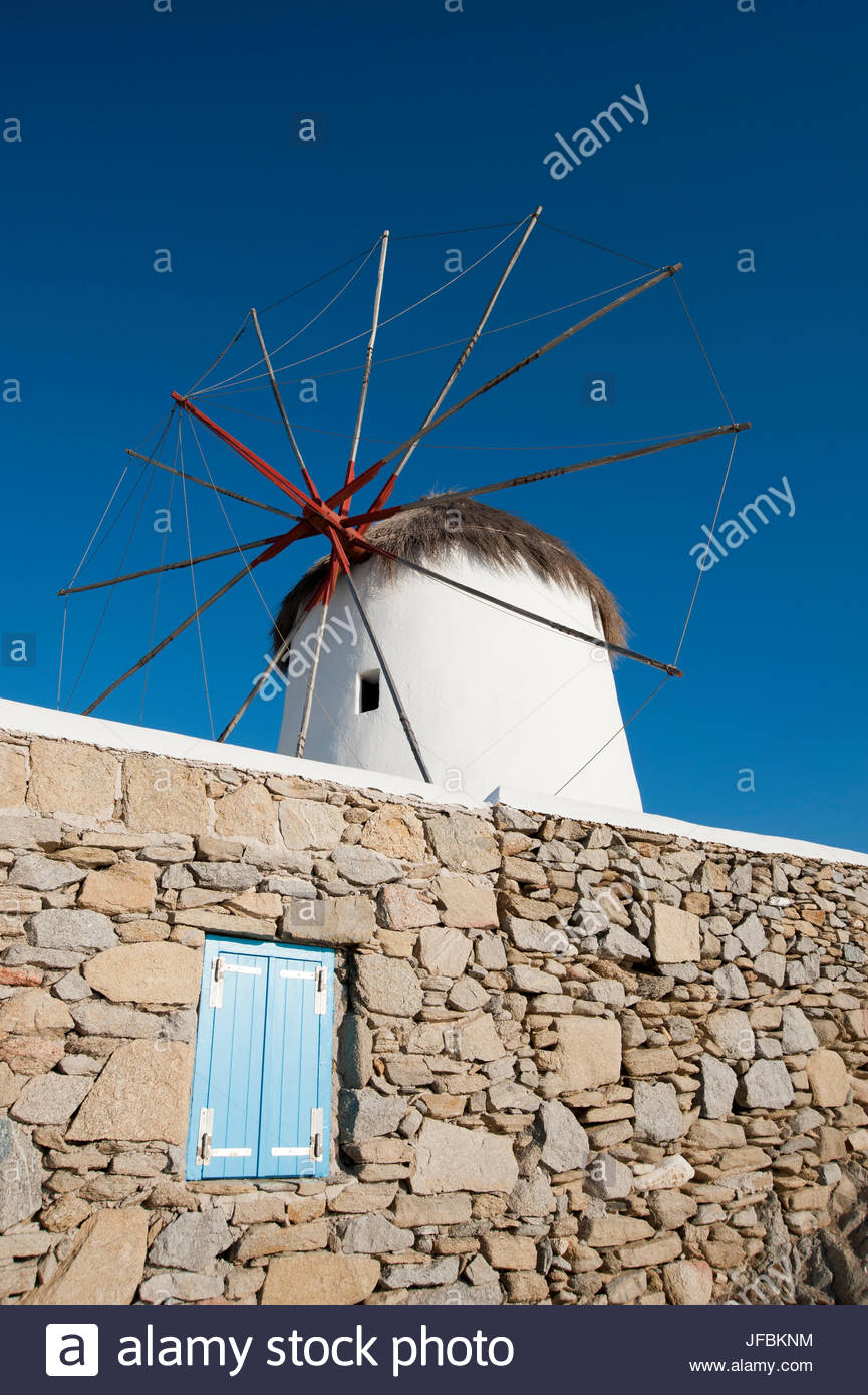 A traditional windmill set behind a rock masonry wall. - Stock Image