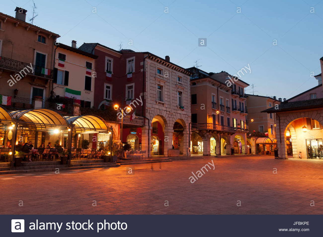 Desenzano del Garda, lined with romantically lit restaurants and shops at dusk. - Stock Image