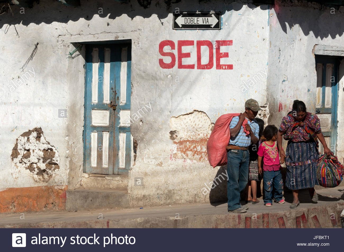 A family on a street corner in the colonial town of Momostenango. - Stock Image