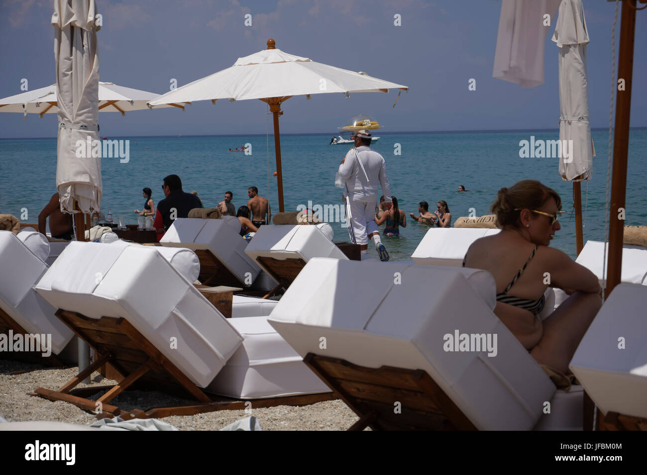 Beach vendor selling corn balancing the plate on his head on a hot summer day by a beach bar with sun decks. - Stock Image