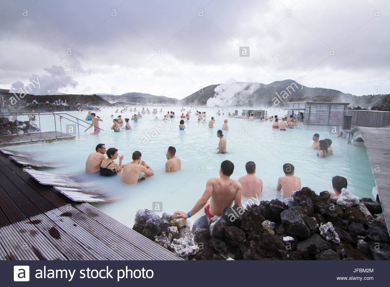 People relaxing in the geothermal hot springs at Blue Lagoon. - Stock Image