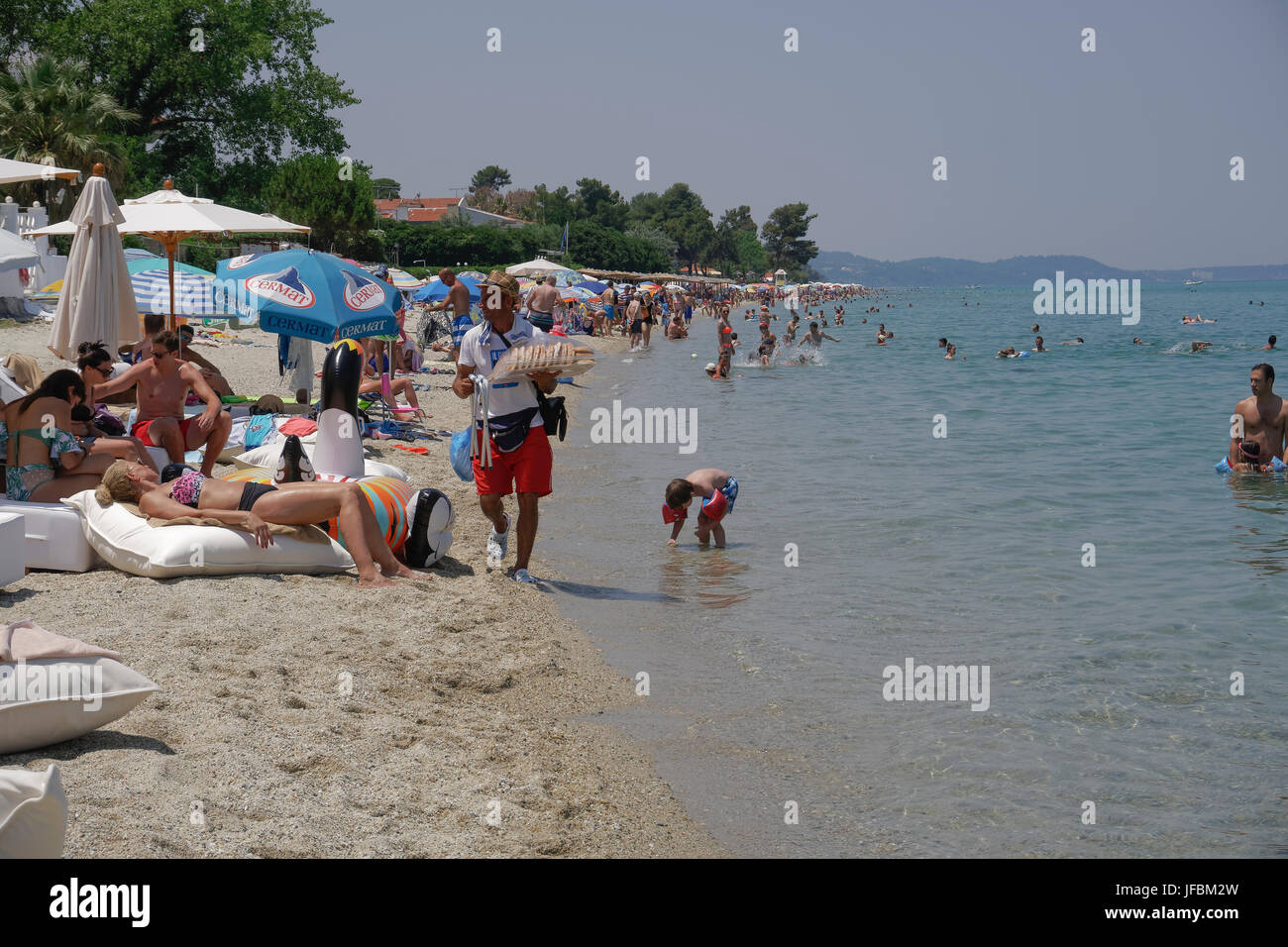 Beach vendor selling Greek donut carrying the plate with his hand on a hot summer day by a beach bar. - Stock Image