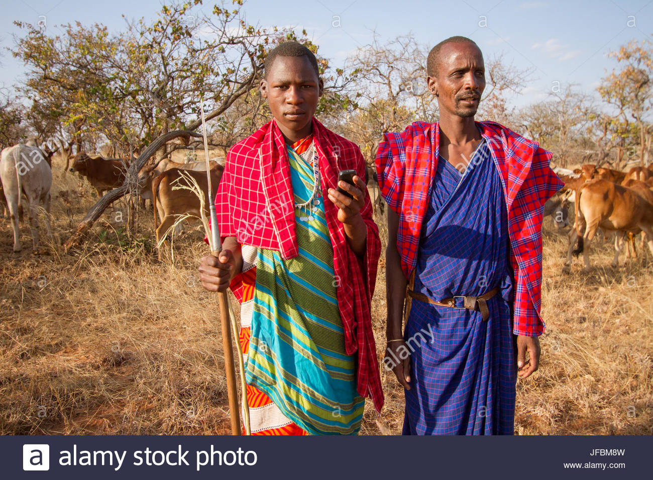 As a semi-nomadic people, the Massai use cell phones to keep in touch with their families and other Massai in the - Stock Image