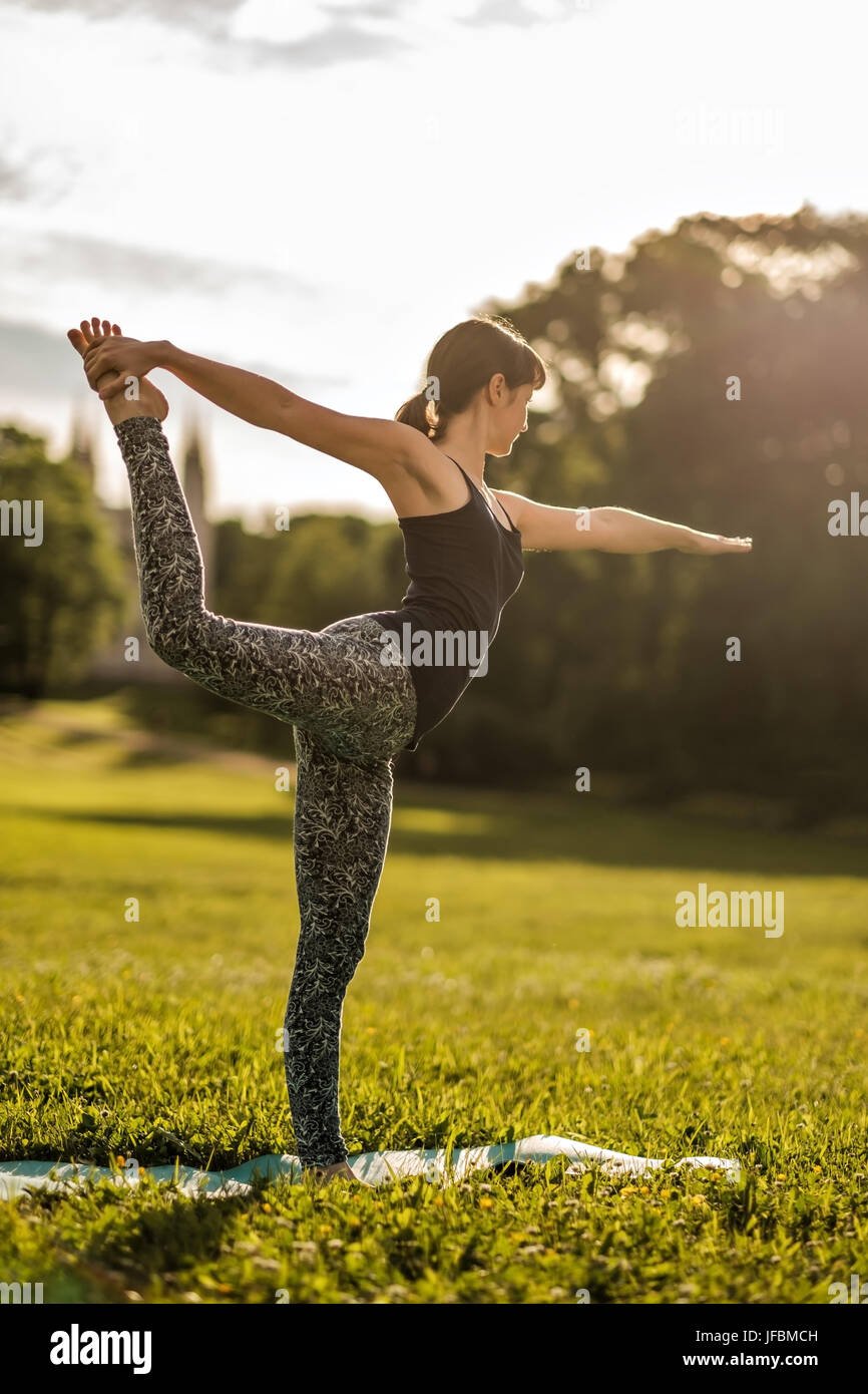 Young attractive woman doing dancers yoga pose outdoors on field - Stock Image