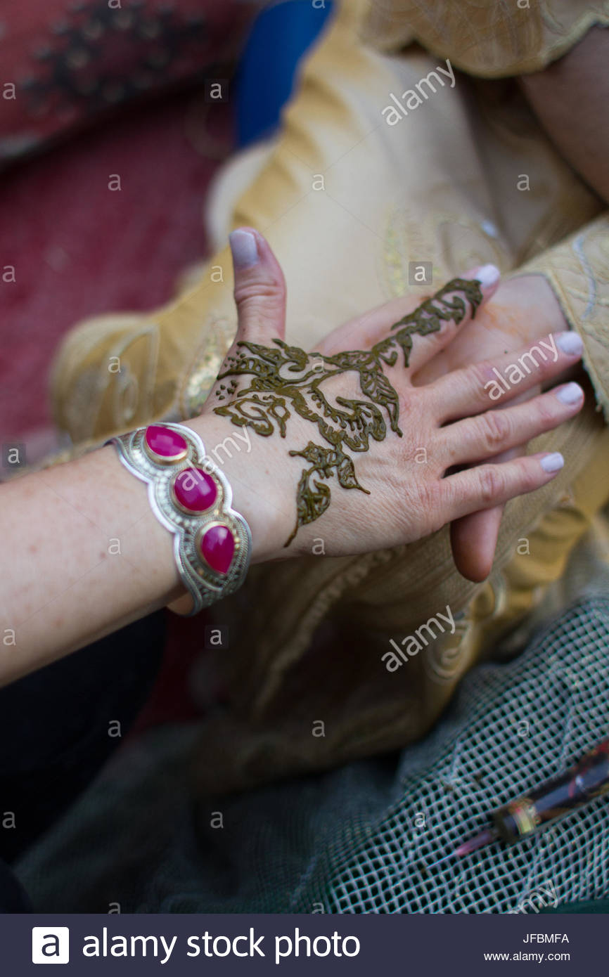 Freshly applied henna drying on a woman's hand. - Stock Image