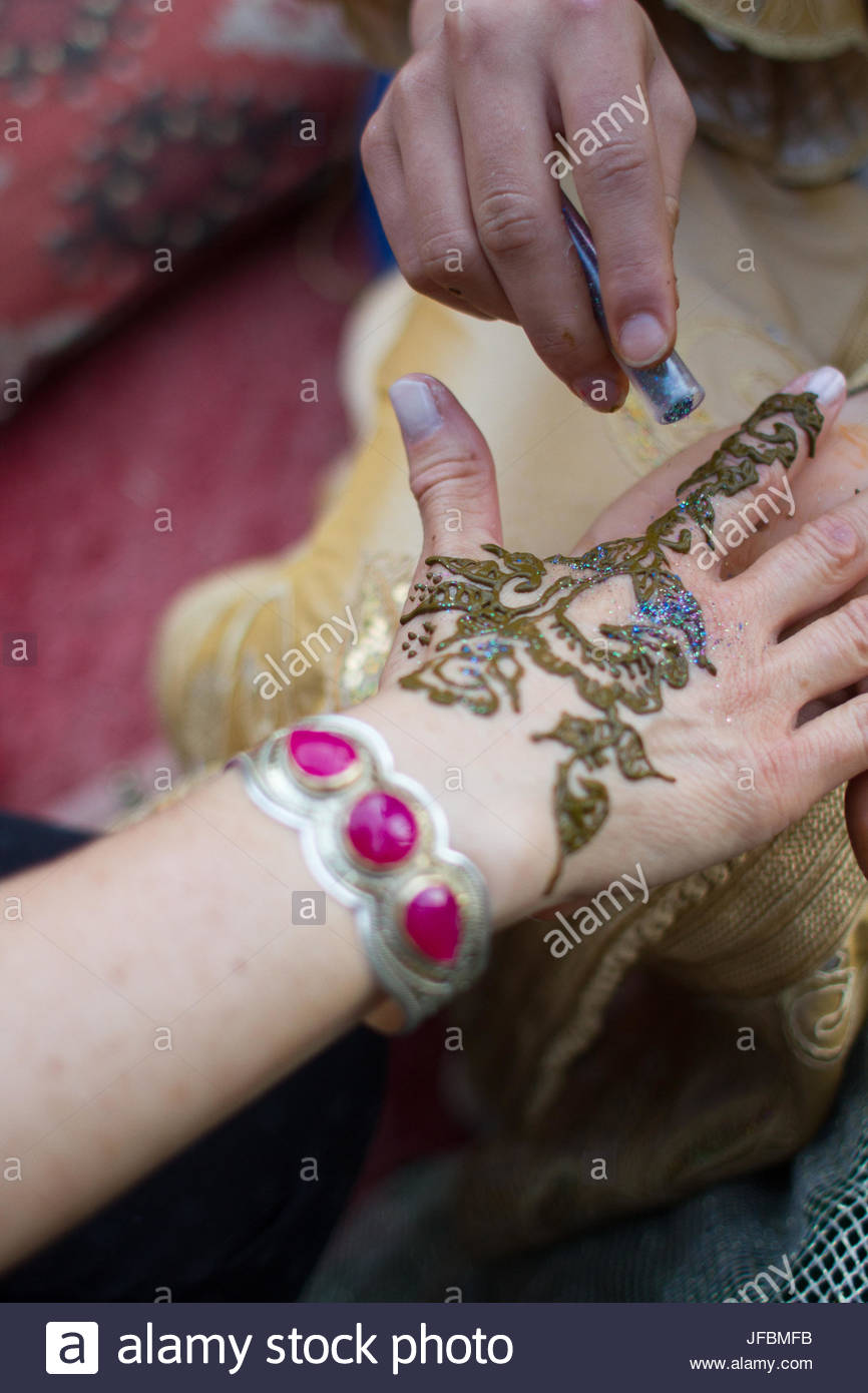 Freshly applied henna, with blue sparkles, drying on a woman's hand. - Stock Image
