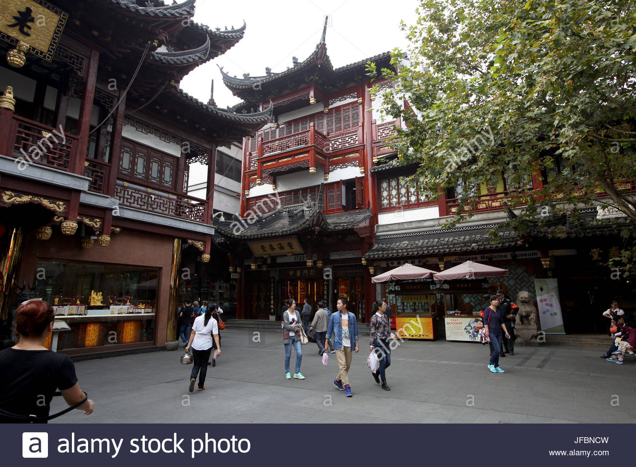 Tourists walk past traditional architecture in the Yuyuan Garden. - Stock Image