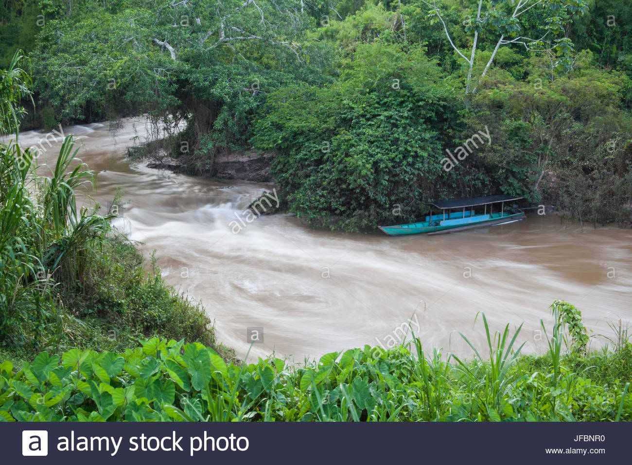 A boat anchored in a swiftly-moving stream that feeds into the Tambopata River. - Stock Image