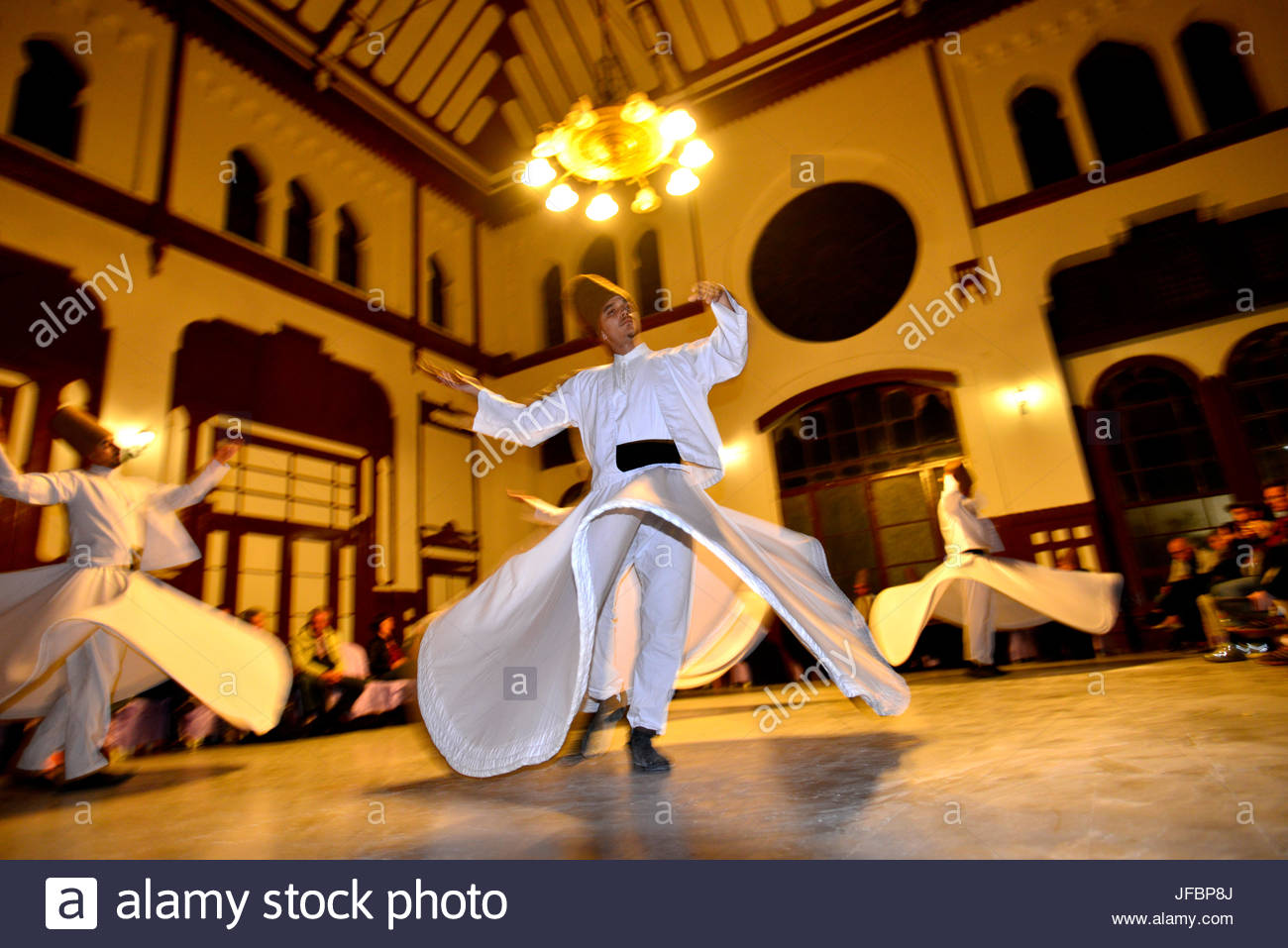 Members of the Mevlevi Sufi Order, whirling dervishes perform at the Sirkeci Central Train Station. - Stock Image