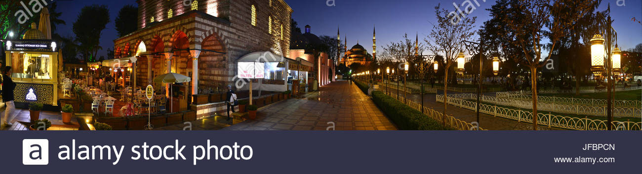 A 180 degree view of a restaurant lined street with the Blue Mosque in the distance. - Stock Image